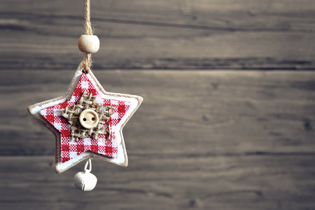 jingle bell: Christmas star with jingle bell against wooden background Stock Photo