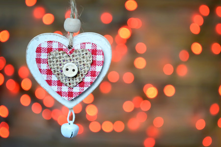 jingle bell: Christmas ornament: Wooden heart with jingle bell against Christmas lights