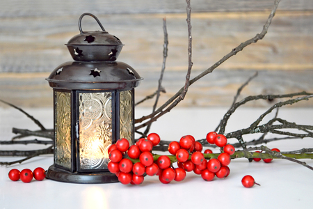 Christmas greeting card with lantern, twigs and red berries on it