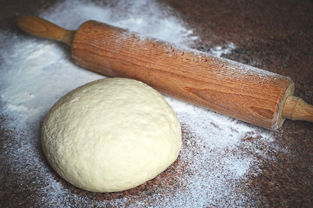 pin board: Fresh dough and rolling pin on kitchen board Stock Photo
