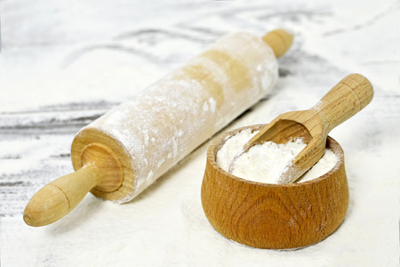 Wheat flour in wooden bowl and rolling-pin