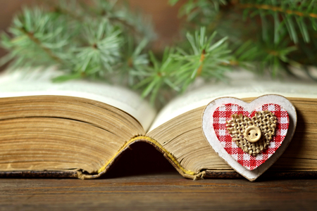 Christmas card: Heart-shaped ornament, Christmas berries and an old book