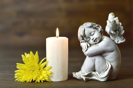 Angel, candle and flower on wooden background Imagens