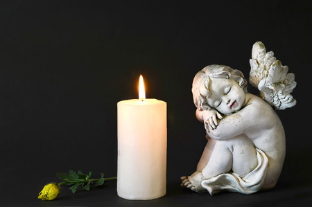 White candle, an angel and flower on dark background