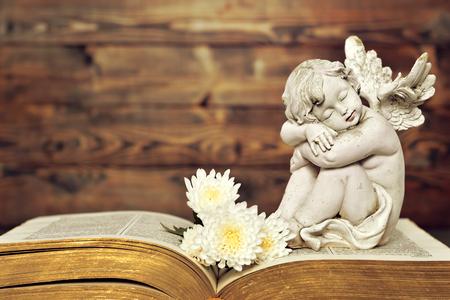 古い本に天使と白の花