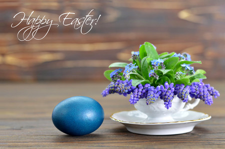 Happy Easter card with Easter egg and spring flowers in tea cup Stock Photo