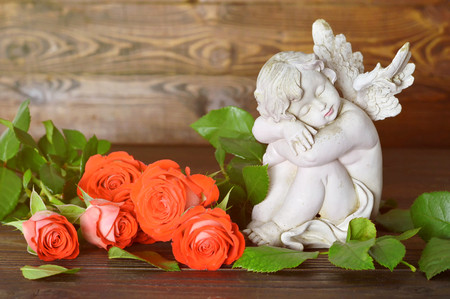 Angel and roses on wooden background