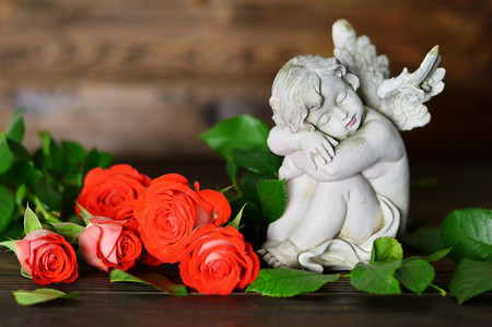 Angel guardian and roses on wooden background  Stock Photo