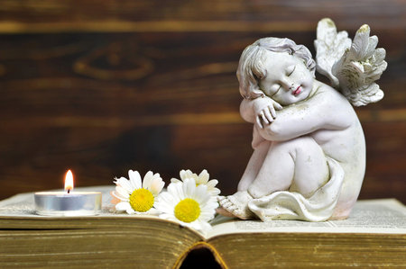 Angel, candle and flowers on wooden background Stock Photo