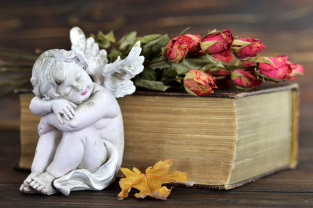 bible flower: Angel, dry roses and old book on wooden background