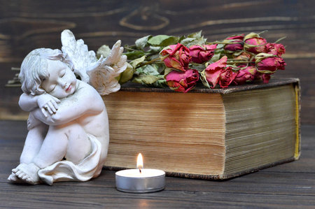 Angel, candle and dry flowers on wooden background Stock Photo
