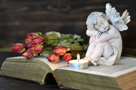 Angel, candle and dry roses on wooden background Stockfoto