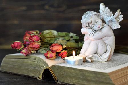 Ngel, vela y rosas secas sobre fondo de madera Foto de archivo - 82490307