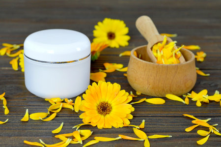 Herbal cosmetic calendula cream on wooden background Stock Photo