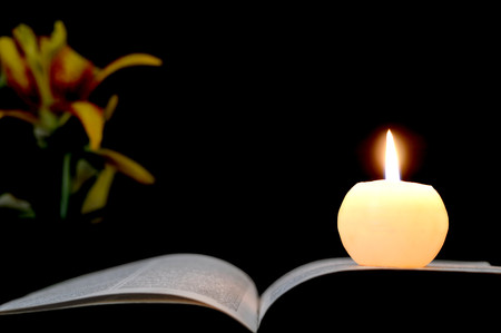 Kaars, geopend boek en bloemen geïsoleerd op zwarte achtergrond Stockfoto