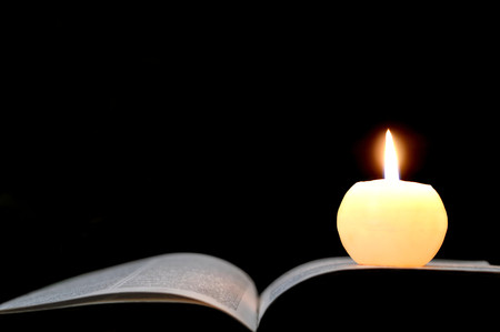 Candle and opened book isolated on black background Banco de Imagens