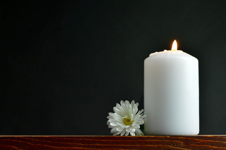 Burning candle and white flower