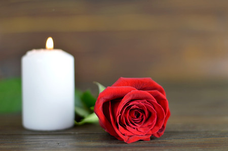 Candle and rose on wooden background