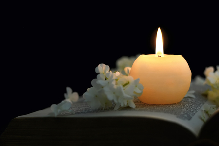 Burning candle and white flowers on opened book