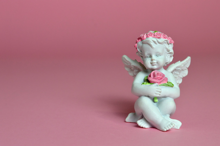 Angel figurine on pink background
