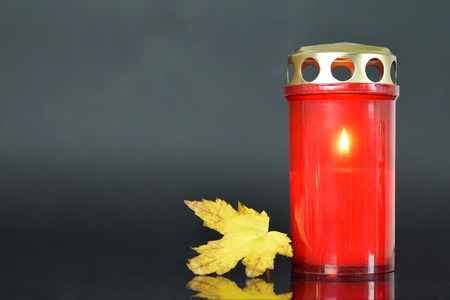 All Soul's Day. Memorial candle and autumn leaf Фото со стока