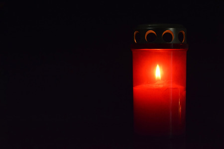 Votive candle on dark background