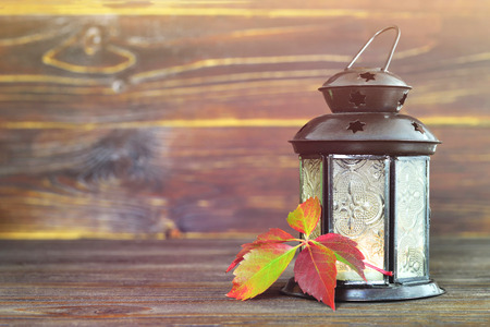 Autumn background with vintage lantern and red leaf