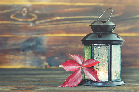 Thanksgiving background with vintage lantern and red leaf