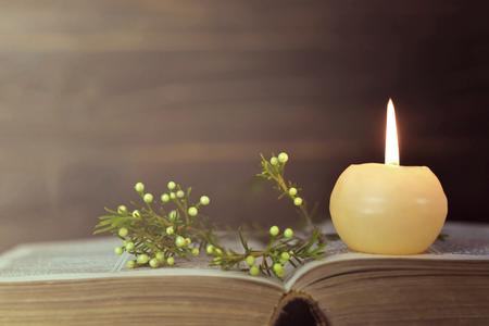 Kerze, Buch und Blumen