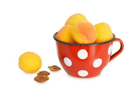 Apricots in vintage cup isolated on white background