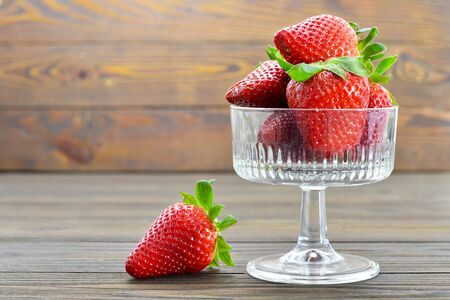 Bowl of fresh strawberries on wooden background 写真素材