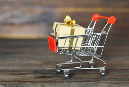 Shopping cart with Christmas gift box on wooden background