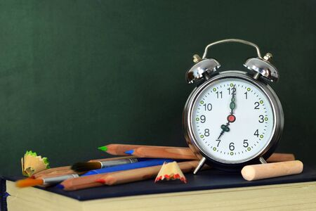 Back to school background with blank blackboard, school supplies and alarm clock