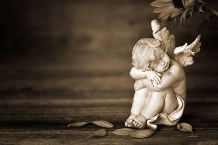 Guardian angel on dark wooden background