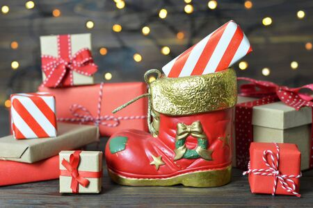 Santa's shoe and gifts on wooden background