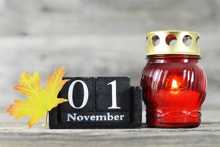 All saints Day. Votive candle, wooden calendar and yellow autumn leaf