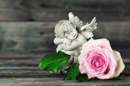 Angel and rose on old wooden background Banco de Imagens