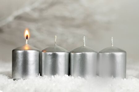 Four Advent candles. One candle burning