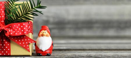 Christmas background with copy space. Santa Claus figurine and Christmas gift on wooden background. Stok Fotoğraf