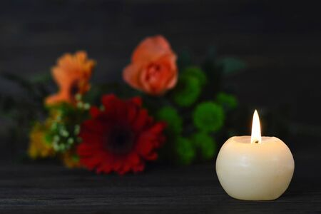 Condolence card with burning candle and flowers on dark background