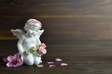 Angel and spring flowers on wooden background