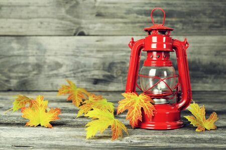 Autumn composition with vintage oil lamp and autumn leaves