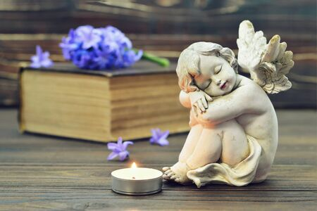 Angel, burning candle and hyacinth flower on the book