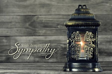 Sympathy card with burning candle on wood background Imagens