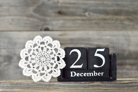 Wooden retro calendar with the date of Christmas and lace doily