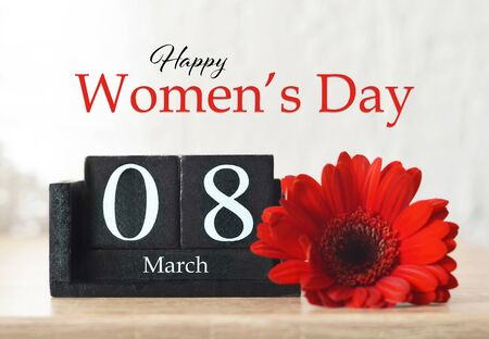 Happy International Womens Day card. Wooden calendar and red gerbera flower