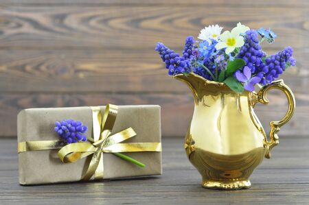 Gift box and flowers on wooden background