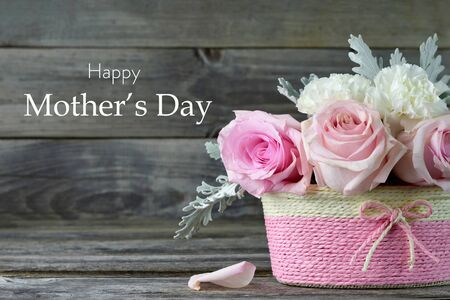 Mothers Day card. Pink roses in basket on wooden background