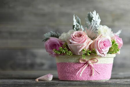 Mothers Day flowers. Pink roses in basket on wooden background Zdjęcie Seryjne