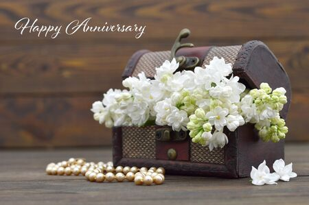 Happy Anniversary card. White lilac flowers in wooden chest